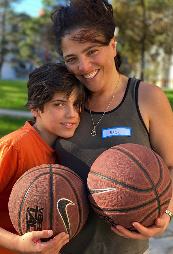mother and son standing together holding basket balls smiling